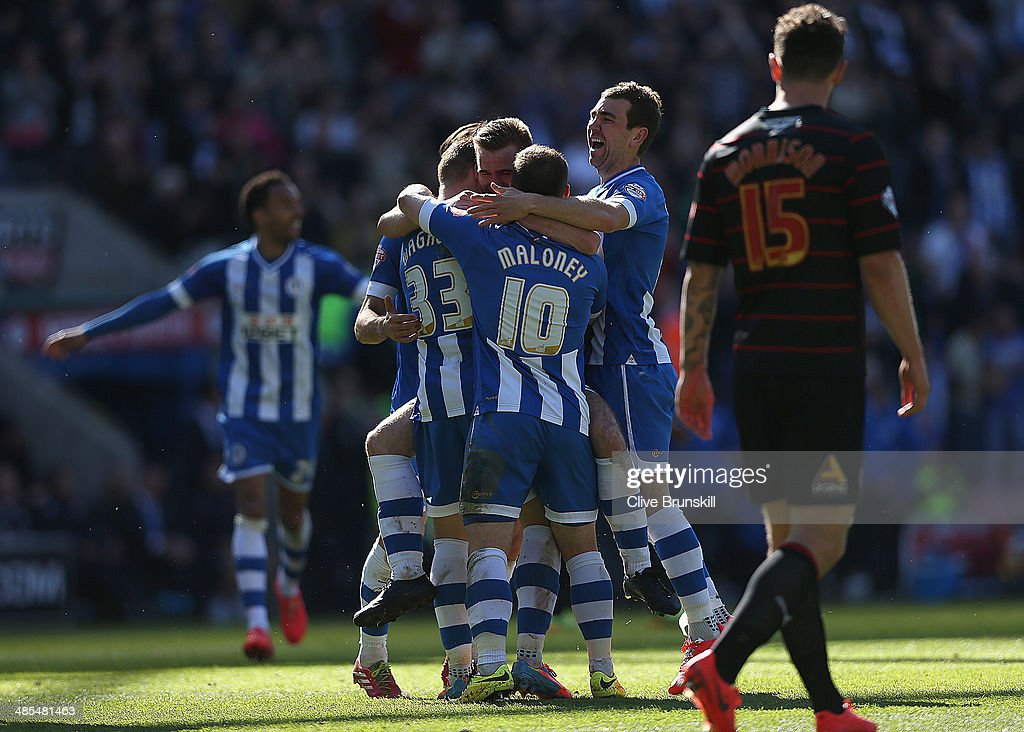 James McArthur of Wigan celebrates team mate Callum McManaman of Wigan Athletic's third goal during the Sky Bet Championship match between Wigan Athletic and Reading at DW Stadium on April 18, 2014 in Wigan, England.