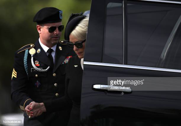 James McCain helps his mother Cindy McCain out of a car as they wait to escort the casket of the late US Sen John McCain to a hearse to travel to a...