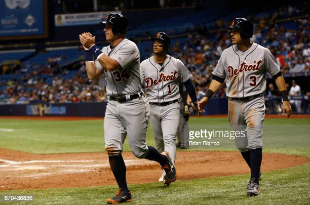 James McCann Jose Iglesias Ian Kinsler of the of the Detroit Tigers acknowledge Nicholas Castellanos at third base after scoring on his triple during...