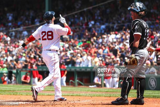 James McCann of the Chicago White Sox looks on as JD Martinez of the Boston Red Sox reacts as he crosses home plate after hitting tworun home run in...