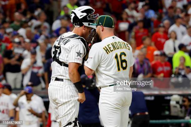 James McCann of the Chicago White Sox talks with Liam Hendriks of the Oakland Athletics on the mound during the 90th MLB AllStar Game at Progressive...
