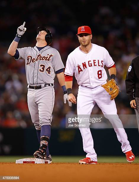 James McCann of the Detroit Tigers celebrates after hitting a double to right field as Taylor Featherston of the Los Angeles Angels looks on in the...