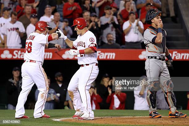 James McCann of the Detroit Tigers looks on as Kole Calhoun congratulates Mike Trout of the Los Angeles Angels of Anaheim after Trout hit a threerun...