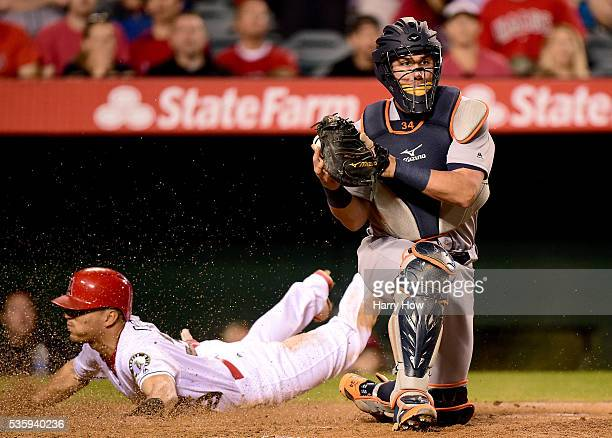 James McCann of the Detroit Tigers prepares to make a throw to first base as Rafael Ortega of the Los Angeles Angels slides to score a run to take a...