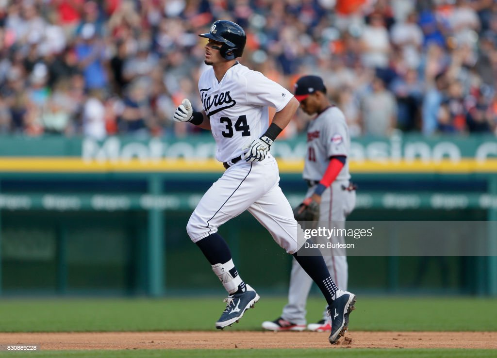James McCann #34 of the Detroit Tigers rounds the bases past Jorge Polanco #11 of the Minnesota Twins after hitting a grand slam against the Minnesota Twins during the first inning at Comerica Park on August 12, 2017 in Detroit, Michigan.