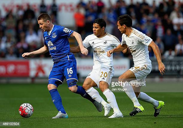 James McCarthy of Everton competes for the ball against Jefferson Montero and Jack Cork of Swansea City during the Barclays Premier League match...