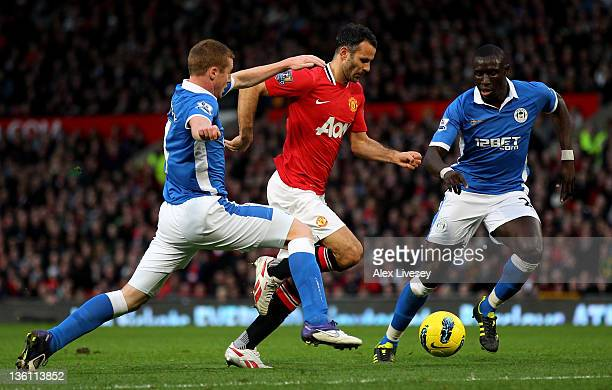 James McCarthy of Wigan Athletic challenges Ryan Giggs of Manchester United during the Barclays Premier League match between Manchester United and...