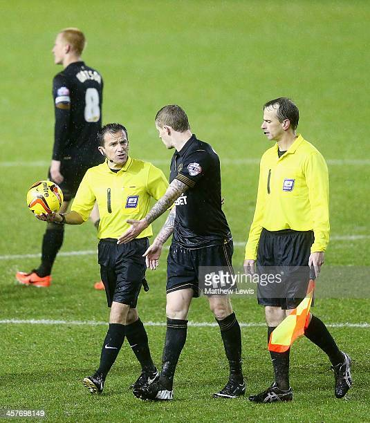 James McClean of Wigan Athletic talks to referee Keith Stroud after the match is called off due to a waterlogged pitch during the Sky Bet...