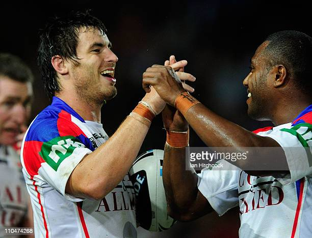 James McManus is congratulated by Akuila Uate of the Knights after he scored a try during the round two NRL match between the North Queensland...