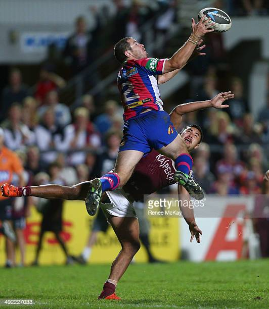 James McManus of the Knights gets to the high ball ahead of Peta Hiku during the round 10 NRL match between the Manly-Warringah Sea Eagles and the...