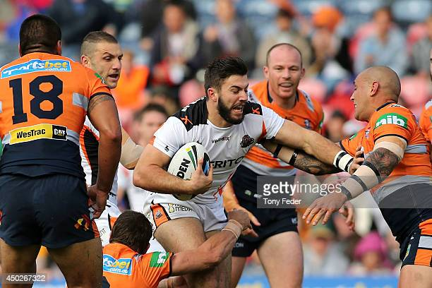 James McManus of the Tigers is tackled by the Knights defence during the round 13 NRL match between the Newcastle Knights and the Wests Tigers at...