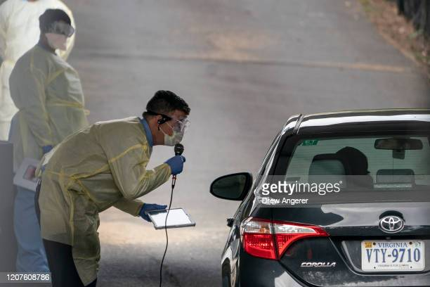 James Meenan director of Virginia Hospital Center outpatient lab gives directions to a patient at a drivethrough coronavirus testing site on March 18...