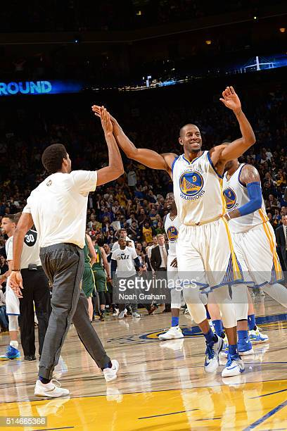 James Michael McAdoo and Andre Iguodala of the Golden State Warriors high five during the game against the Utah Jazz on March 9 2016 at Oracle Arena...