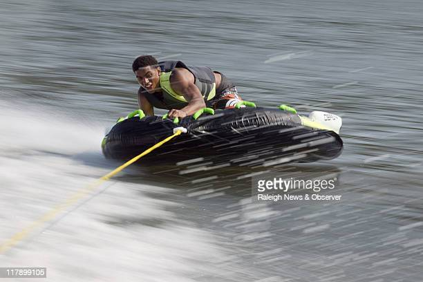 James Michael McAdoo enjoys the speed and the splash as he rides a tube pulled behind a boat in Linkhorn Bay, at Virginia Beach, Virginia, June 1,...