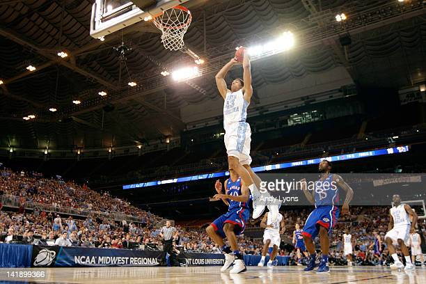 James Michael McAdoo of the North Carolina Tar Heels dunks in the first half against Kevin Young and Elijah Johnson of the Kansas Jayhawks during the...