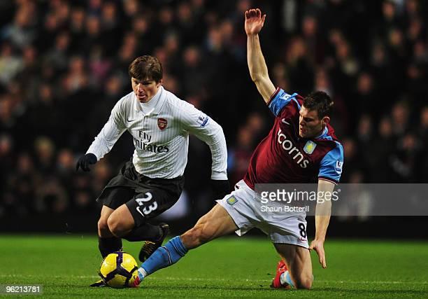 James Milner of Aston Villa tackles Andrey Arshavin of Arsenal during the Barclays Premier League match between Aston Villa and Arsenal at Villa Park...