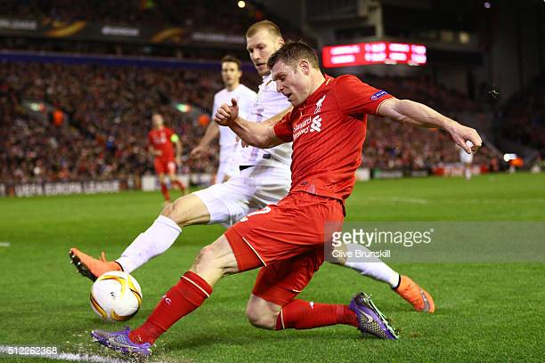 James Milner of Liverpool and Ragnar Klavan of Augsburg compete for the ball during the UEFA Europa League Round of 32 second leg match between...