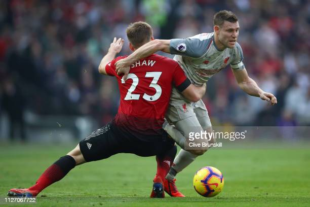 James Milner of Liverpool battles for possession with Luke Shaw of Manchester United during the Premier League match between Manchester United and...