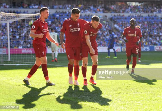 James Milner of Liverpool celebrates after scoring his team's second goal with teammates during the Premier League match between Cardiff City and...