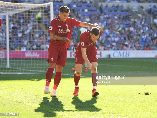 James Milner of Liverpool celebrates after scoring his team's second goal with teammate Roberto Firmino during the Premier League match between...