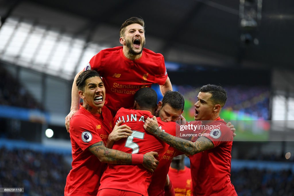 James Milner of Liverpool (R) celebrates scoring his sides first goal with his Liverpool team mates during the Premier League match between Manchester City and Liverpool at Etihad Stadium on March 19, 2017 in Manchester, England.