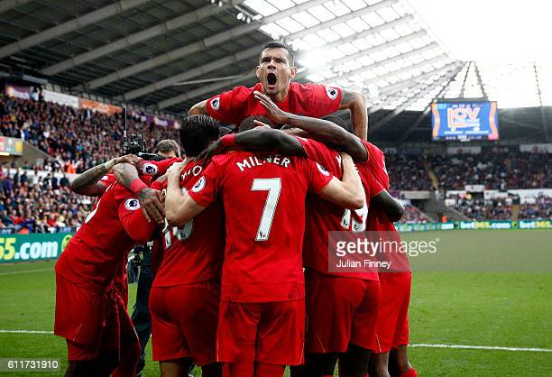 James Milner of Liverpool celebrates scoring his sides second goal with his team mates during the Premier League match between Swansea City and...