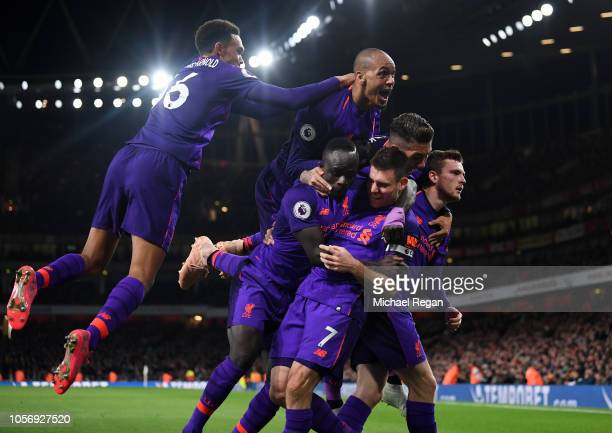 James Milner of Liverpool celebrates with his team after he scores his sides first goal during the Premier League match between Arsenal FC and...