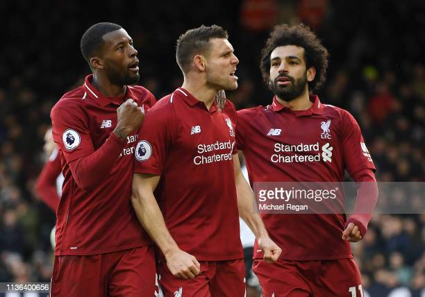 James Milner of Liverpool celebrates with his teammates after he scores his sides second goal from the penalty spot during the Premier League match...