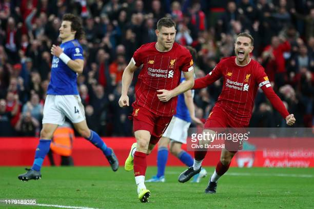 James Milner of Liverpool celebrates with Jordan Henderson of Liverpool after he scores his sides second goal from the penalty spot during the...