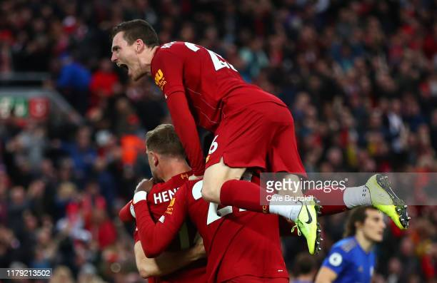 James Milner of Liverpool celebrates with Jordan Henderson of Liverpool and Divock Origi of Liverpool and Andy Robertson of Liverpool after he scores...