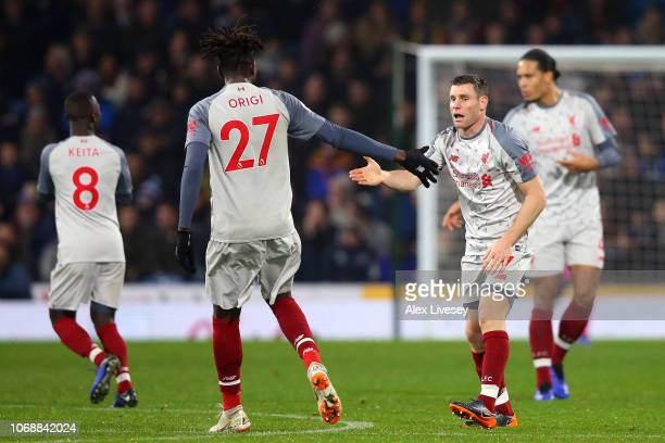 James Milner of Liverpool celebrates with team mate Divock Origi of Liverpool after scoring their team's first goal during the Premier League match...