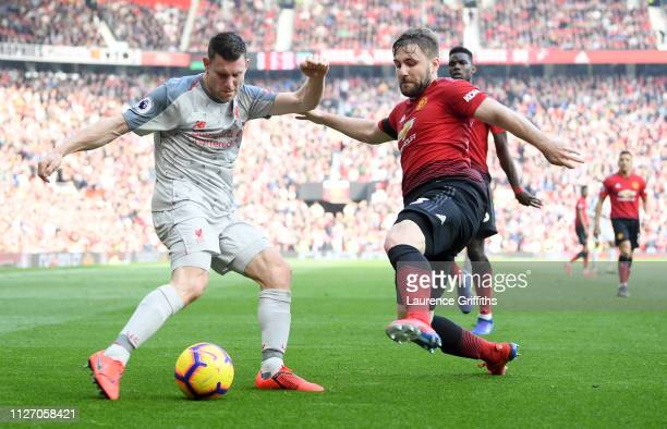 James Milner of Liverpool crosses the ball under pressure from Luke Shaw of Manchester United during the Premier League match between Manchester...
