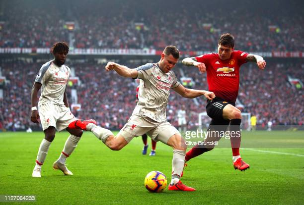 James Milner of Liverpool crosses the ball under pressure from Victor Lindelof of Manchester United during the Premier League match between...
