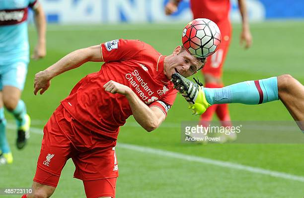 James Milner of Liverpool heads the ball away from a foot during the Barclays Premier League match between Liverpool and West Ham United on August 29...