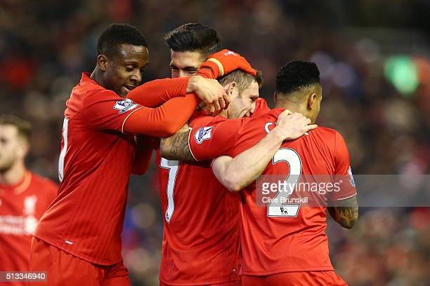 James Milner of Liverpool is mobbed by teammates in celebration Divock Origil and Nathaniel Clyne after scoring his sides second goal during the...