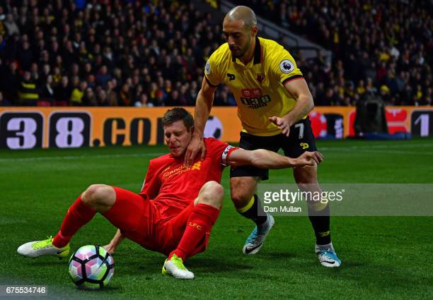 James Milner of Liverpool is tackled by Nordin Amrabat of Watford during the Premier League match between Watford and Liverpool at Vicarage Road on...