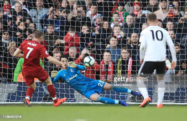 James Milner of Liverpool scores his sides second goal from the penalty spot past Sergio Rico of Fulham during the Premier League match between...