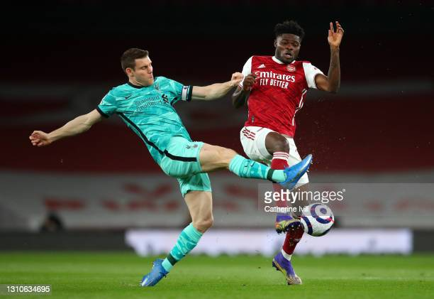 James Milner of Liverpool tackles Thomas Partey of Arsenal during the Premier League match between Arsenal and Liverpool at Emirates Stadium on April...