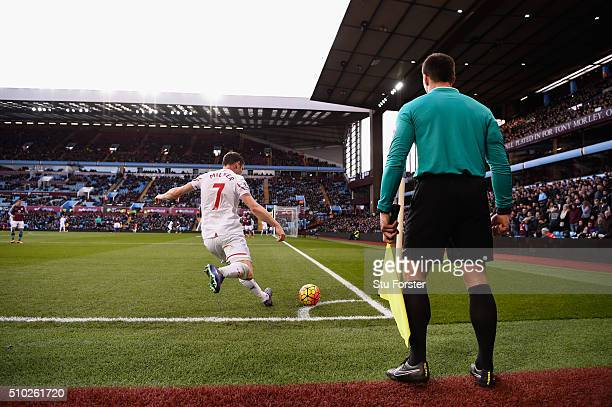 James Milner of Liverpool takes a corner watched by the assistant referee during the Barclays Premier League match between Aston Villa and Liverpool...