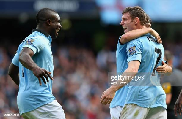 James Milner of Manchester City celebrates scoring his team's third goal with team-mate Micah Richards during the Barclays Premier League match...