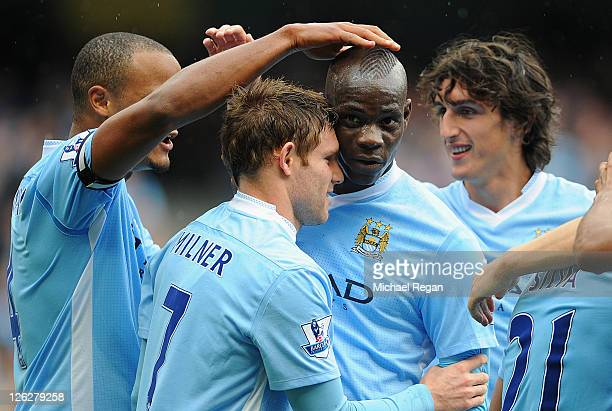 James Milner of Manchester City celebrates scoring to make it 2-0 with team mate Mario Balotelli during the Barclays Premier League match between...