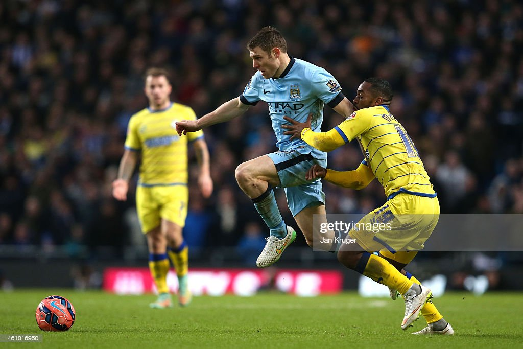James Milner of Manchester City is challenged by Jacques Maghoma of Sheffield Wednesday during the FA Cup Third Round match between Manchester City and Sheffield Wednesday at Etihad Stadium on January 4, 2015 in Manchester, England.