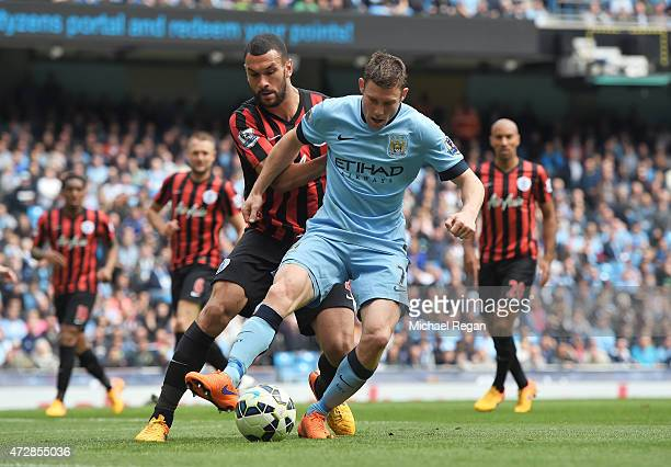 James Milner of Manchester City is challenged by Steven Caulker of QPR during the Barclays Premier League match between Manchester City and Queens...
