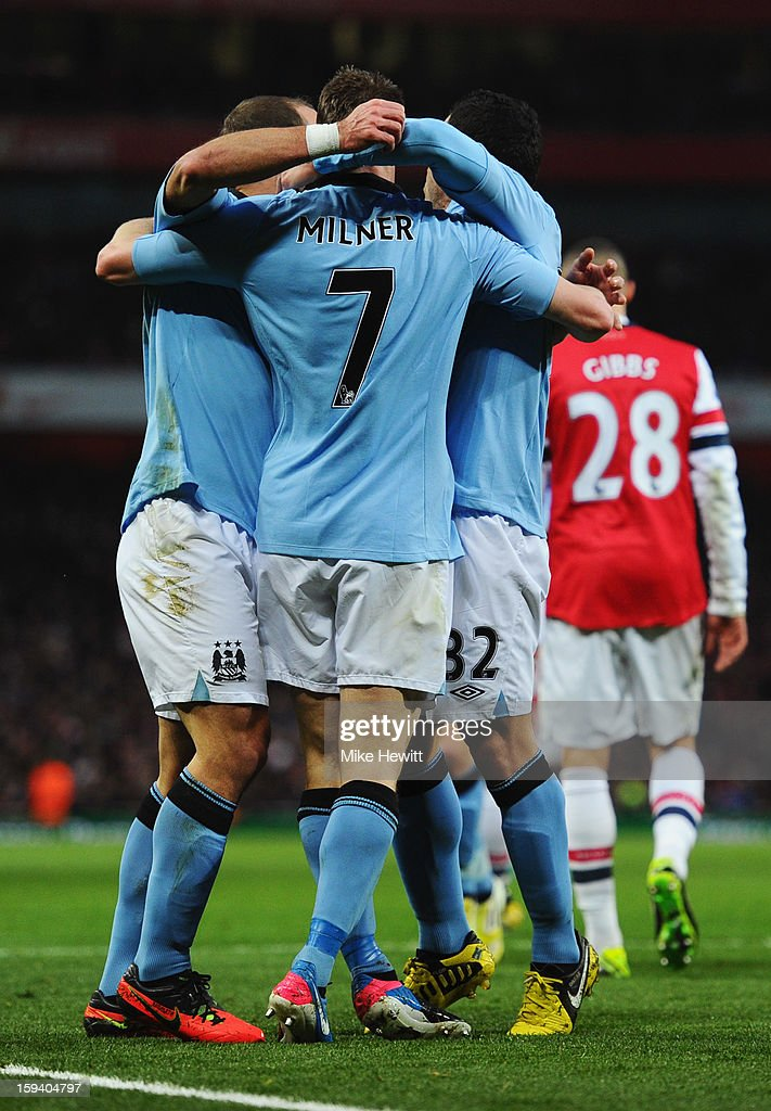 James Milner of Manchester City (7) is congratulated by team mates as he scores their first goal during the Barclays Premier League match between Arsenal and Manchester City at Emirates Stadium on January 13, 2013 in London, England.