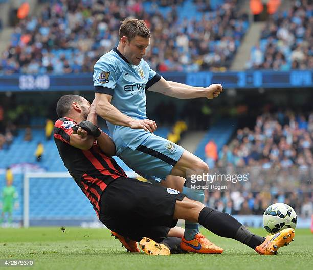 James Milner of Manchester City is tackled by Steven Caulker of QPR during the Barclays Premier League match between Manchester City and Queens Park...