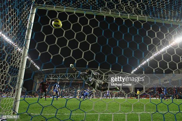 James Milner of Manchester City scores his sides second goal as Ali Al Habsi the goalkeeper of Wigan Athletic dives in vain during the Barclays...