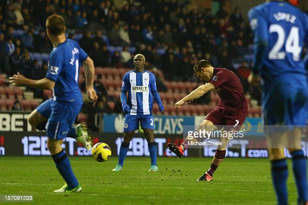 James Milner of Manchester City scores his sides second goal during the Barclays Premier League match between Wigan Athletic and Manchester City at...