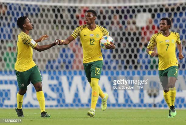 James Monyane of South Africa celebrates with team mates Kobamelo Kodisang of South Africa and Promise Mkhuma of South Africa after scoring his...