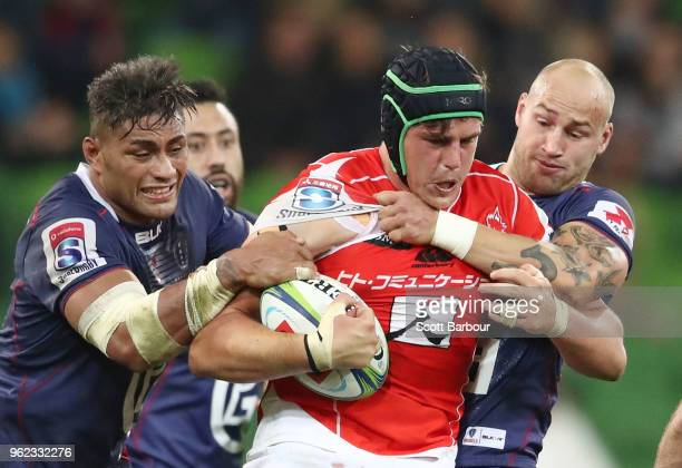James Moore of the Sunwolves is tackled by Bill Meakes and Amanaki Mafi of the Rebels during the round 15 Super Rugby match between the Rebels and...