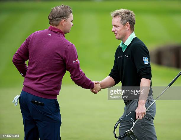 James Morrison of England shakes hands with Luke Donald of England on the 18th hole during day 2 of the BMW PGA Championship at Wentworth on May 22,...